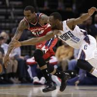 Photo - Washington Wizards' Trevor Booker (35) and Charlotte Bobcats' Kemba Walker (15) during the first half of an NBA basketball game in Charlotte, N.C., Monday, March 31, 2014. (AP Photo/Chuck Burton)