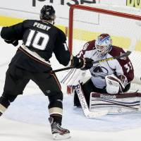 Photo - Anaheim Ducks right wing Corey Perry, left, scores the winning goal past Colorado Avalanche goalie Jean-Sebastien Giguere during overtime of an NHL hockey game in Anaheim, Calif. Sunday, Feb. 24, 2013. The Ducks won 4-3. (AP Photo/Chris Carlson)