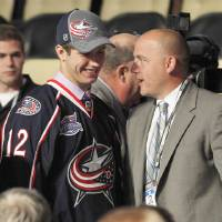 Photo -   Ryan Murray, left, a defenseman, stands with officials from the Columbus Blue Jackets at their table after being chosen second overall in the first round of the NHL hockey draft on Friday, June 22, 2012, in Pittsburgh. (AP Photo/Keith Srakocic)