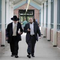 Photo - Yosef Kolko, 39, right, walks with an unidentified man, near the Ocean County Courthouse in Toms River, N.J., Thursday, May 9, 2013, during a break in his trial on sexual assault charges. Testimony continues in the trial of the yeshiva teacher accused of sexually abusing a boy at a summer camp where he was a counselor. Prosecutors say the boy's parents were pressured by members of their Orthodox Jewish community to drop the charges and let a rabbinical court deal with them. (AP Photo/Mel Evans)