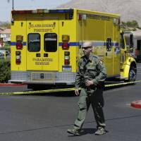 Photo - A Las Vegas Metropolitan Police officer walks near the scene of a shooting, Sunday, June 8, 2014 in Las Vegas. Police say two suspects shot two officers at a Las Vegas pizza parlor before fatally shooting a person and turning the guns on themselves at a nearby Walmart. (AP Photo/John Locher)