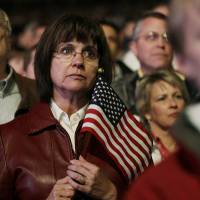 Photo -   A woman holds a U.S. flag as she and others listen to a speech by Republican presidential candidate, former Massachusetts Gov. Mitt Romney, during a campaign rally in Greenwood Village, Colo. in south Denver on Saturday, Nov. 3, 2012. (AP Photo/Brennan Linsley)