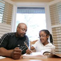 Photo -   In this April 17, 2012 photo, Roger Witherspoon helps his daughter, Gabrielle, 9, with her homework in Nashville, Tenn. Tennessee is one of only a few states that has passed laws creating evaluations or contracts that put helping with homework or attending teacher conferences into writing. (AP Photo/Mark Humphrey)