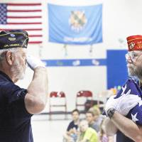 Photo - Don Kasper salutes the flag held by Harmon Thompson during a flag folding demonstration.
