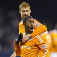 Photo -   Houston Dynamo's Corey Ashe (26) and Andre Hainault celebrate after an MLS soccer playoff game against Sporting Kansas City, Wednesday, Nov. 7, 2012, in Kansas City, Kan. Houston lost 1-0 on Wednesday, but advanced with a 2-1 aggregate-goal result. (AP Photo/Ed Zurga)