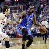 Photo - Oklahoma City Thunder forward Kevin Durant, right, dribbles against Portland Trail Blazers forward Victor Claver, from Spain, during the first quarter of an NBA basketball game in Portland, Ore., Friday, April 12, 2013. (AP Photo/Don Ryan) ORG XMIT: ORDR108