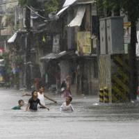 Photo -   Children play in floodwaters following heavy monsoon rains spawned by a tropical depression in Manila, Philippines, Saturday July 21, 2012. The heavy rains flooded most parts of metropolitan Manila Saturday forcing cancellation of classes, creating massive traffic jams and closure of some businesses. (AP Photo/Bullit Marquez)