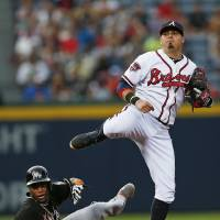 Photo - Atlanta Braves second baseman Ramiro Pena (14) avoids Miami Marlins shortstop Adeiny Hechavarria (3) as he tries to turn a double play on a Christian Yelich ground ball in the fifth inning of a baseball game  Thursday, July 24, 2014 in Atlanta. Yelich was safe at first base. (AP Photo)