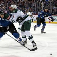 Photo - Minnesota Wild defenseman Clayton Stoner (4) pushes Colorado Avalanche center Ryan O'Reilly away from the puck during the first period of an NHL hockey game in Denver on Saturday, Dec. 14, 2013. (AP Photo/Joe Mahoney)