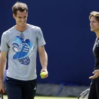 Photo - Andy Murray is joined by new coach Amelie Mauresmo, right, at a practice session at The Queen's Club in London, Wednesday June 11, 2014. Murray starts the defence of his title at Queen's Club tournament Wednesday, just hours after beginning with his new coach Mauresmo. (AP Photo / Jonathan Brady, PA) UNITED KINGDOM OUT - NO SALES - NO ARCHIVES