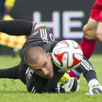 Photo - Montreal Impact goalkeeper Evan Bush keeps his eyes on the ball as Chicago Fire's Mike Magee (9) moves in during the first half of an MLS soccer game Saturday, Aug. 16, 2014, in Montreal. (AP Photo/The Canadian Press, Graham Hughes)