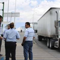 Photo -   FILE - In this July 5, 2012 file photo, attorney Emilio de La Rosa, left, and forensics expert Mario Gomez, right, talk to customs and court officials at the Las Americas Bridge in Juarez, Mexico while doing a reconstruction of the events that lead to the arrest of trucker Jabin Bogan. Bogan, a Dallas trucker detained for eight months in Mexico on allegations that he tried to smuggle assault rifle ammunition into the country, is expected to return Friday, Nov. 23, 2012, to the United States, his lawyer said. (AP Photo/ Juan Carlos Llorca, File)