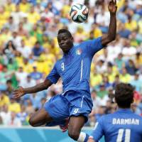 Photo - Italy's Mario Balotelli, top, collides with Uruguay's Alvaro Pereira, bottom, during the group D World Cup soccer match between Italy and Uruguay at the Arena das Dunas in Natal, Brazil, Tuesday, June 24, 2014. (AP Photo/Antonio Calanni)