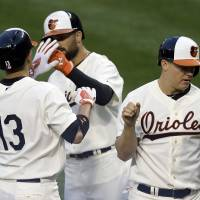 Photo - Baltimore Orioles' Manny Machado (13) high-fives teammates Nick Markakis, center, and Nick Hundley after driving them in on a home run in the second inning of an interleague baseball game against the St. Louis Cardinals, Friday, Aug. 8, 2014, in Baltimore. (AP Photo/Patrick Semansky)