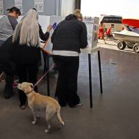 Photo -   Voters cast ballots as lifeguards maneuver a personal watercraft at the polling place at the Venice Beach lifeguard headquarters in Los Angeles Tuesday, Nov. 6, 2012. After a grinding presidential campaign, Americans are heading into polling places across the country.(AP Photo/Reed Saxon)