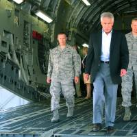 Photo - In this photo taken July 17, 2013, Defense Secretary Chuck Hagel, flanked by Air Force personnel, walks down the rear ramp of a C-17 at Joint Base Charleston near Charleston, S.C., on the last day of a three-day trip to visit bases in the Carolinas and Florida. When Hagel told civilian Department of Defense workers on the base that job furloughs, that have forced a 20% pay cut on most of the military's civilian workforce, will likely continue next year, and may get even worse, the audience softly gasped in surprise and gave a few depressed low whistles. He said that if the department has to absorb another $52 billion in cuts next year because of the federal sequester, there will likely be layoffs instead of furloughs. (AP Photo/Bruce Smith)