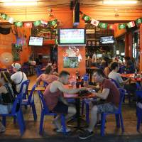 Photo - Tourists and locals eat and drink at a restaurant in Bangkok's Khaosan road, Thailand, Saturday June 14, 2014. The generals who seized power in Thailand have lifted a nationwide curfew, giving a green light for the capital's red-light districts, nightclubs and pubs to roar back to life. Late night revelry was planned in Bangkok to celebrate the return of Saturday night freedom for the first time in a month. (AP Photo/Apichart Weerawong)