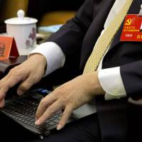 Photo -   In this Nov. 9, 2012 photo, Communist Party delegate Zheng Yanxiong uses his laptop during a group discussion meeting as part of the 18th Communist Party Congress at the Great Hall of the People in Beijing, China. During China's last party congress, the cadres in charge of the world's most populous nation didn't know a hashtag from a hyperlink. But five years on, there's a new message from Beijing: The political transition will be microblogged. (AP Photo/Alexander F. Yuan)