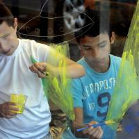Photo - Above: Jesus De La Torre, 11, and Baltazar Nino, 14, paint a mural at Southern Oaks Library at a summer reading program kickoff event Wednesday.