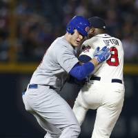 Photo - Chicago Cubs' Anthony Rizzo, left, is tagged out by Atlanta Braves left fielder Justin Upton (8) after being caught in a rundown between first and second base in the fourth inning of a baseball game on Saturday, May 10, 2014, in Atlanta. (AP Photo/John Bazemore)