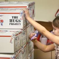 Photo - Rebekah Chandler, 6, writes cheerful notes on the outside of care boxes before they are taken to a truck. Chandler has helped with the HUGS Project for a couple of years. Photos by Jim Beckel, The Oklahoman