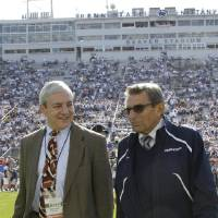 """Photo -   FILE - In this Oct. 8, 2011, file photo Penn State president Graham Spanier, left, and head football coach Joe Paterno talk before an NCAA college football game against Iowa in State College, Pa. Spanier is accused of perjury, endangering children and other charges in the Jerry Sandusky molestation scandal. According to online court records charges were filed, Thursday, Nov. 1, 2012, against Penn State's ex-president and two other administrators in what prosecutors called """"a conspiracy of silence."""