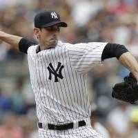 Photo - New York Yankees starting pitcher Brandon McCarthy throw during the first inning of a baseball game against the Cincinnati Reds, Saturday, July 19, 2014, at Yankee Stadium in New York. (AP Photo/Julio Cortez)