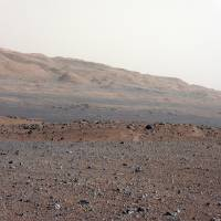 Photo -   In this image released by NASA on Monday, Aug. 27, 2012, an image taken by the Mast Camera (MastCam) highlights the geology of Mount Sharp, a mountain inside Gale Crater, where the rover landed. Prior to the rover's landing on Mars, observations from orbiting satellites indicated that the lower reaches of Mount Sharp, below the line of white dots, are composed of relatively flat-lying strata that bear hydrated minerals. Those orbiter observations did not reveal hydrated minerals in the higher, overlying strata. The MastCam data now reveal a strong discontinuity in the strata above and below the line of white dots, agreeing with the data from orbit. Strata overlying the line of white dots are highly inclined (dipping from left to right) relative to lower, underlying strata. The inclination of these strata above the line of white dots is not obvious from orbit. This provides independent evidence that the absence of hydrated minerals on the upper reaches of Mount Sharp may coincide with a very different formation environment than lower on the slopes. The train of white dots may represent an
