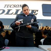 Photo - Officer Monica Vannorman, center, photographs a pistol as Officer Merri Hughes, right, logs relinquished weapons at a gun buyback event on Tuesday, Jan. 8, 2013, at the Tucson Police Department Midtown Substation in Tucson, Ariz. Gun owners relinquished their handguns and rifles in exchange for a $50 Safeway gift card on Tuesday, which marked the second anniversary of the shootings in Tucson that left six dead and 13 injured, including former Rep. Gabrielle Giffords.  (AP Photo/Arizona Daily Star, Mike Christy)  ALL LOCAL TV OUT; PAC-12 OUT; MANDATORY CREDIT; NO SALES; MAGS OUT