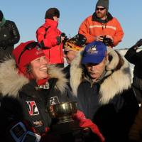 Photo - Aliy Zirkle accepts the Wells Fargo Gold Coast Award for the first musher to reach the Bering Sea in Unalakleet during the 2014 Iditarod Trail Sled Dog Race on Saturday, March 8, 2014. (AP Photo/The Anchorage Daily News, Bob Hallinen)