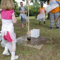 Photo - Children retreat as soda begins to spew from a plastic soda bottle. Children were taking part in the Diet Coke and Mentos science experiment   Photo by Jim Beckel, The Oklahoman   Jim Beckel - THE OKLAHOMAN