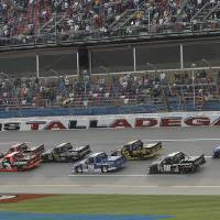 Photo - Trucks race through the tri-oval at the start of the NASCAR Trucks auto race at Talladega Superspeedway in Talladega, Ala., Saturday, Oct. 19, 2013. (AP Photo/Dave Martin)