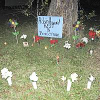 Photo - A makeshift for Robin Leander Howard at the base of a tree in the 1400 block of Monticello Court.  A candelight vigil honoring his life was held there Sunday night.  MATT DINGER