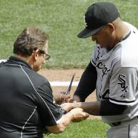 Photo - A trainer removes a bracelet from the left arm of Chicago White Sox relief pitcher Ronald Belisario, right, during the seventh inning of a baseball game against the Minnesota Twins in Minneapolis, Sunday, July 27, 2014. The Twins won 4-3. (AP Photo/Ann Heisenfelt)