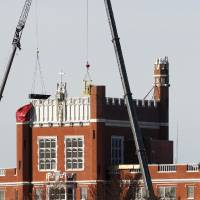Photo - Men work from inside a basket attached to a crane to remove individual bricks from the southeast turret on Benedictine Hall last year. Photo by JIM BECKEL, THE OKLAHOMAN ARCHIVES