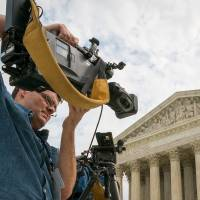 Photo -  A videojournalist sets up Tuesday outside the Supreme Court in Washington. The court is hearing oral arguments between over-the-air broadcasters and Aereo, Inc., an Internet startup company that gives subscribers access to television on their laptops and other portable devices. AP Photo   J. David Ake -  AP