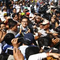 Photo - Opposition Cambodia National Rescue Party leader Sam Rainsy, center, is surrounded by members of press upon arrival at Phnom Penh International Airport, in Phnom Penh, Cambodia, Friday, Aug. 16, 2013. Cambodia's main opposition party filed formal complaints Wednesday over the results of last month's general election, challenging the victory of the ruling Cambodian People's Party and alleging widespread irregularities. The complaints should delay ratification of the results by the National Election Committee until sometime before Sept. 8. (AP Photo/Heng Sinith)