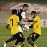 Photo -   United States' Clint Dempsey, center, is challenged by Jamaica's Jason Morrison, left, and Jevaughn Watson during a 2014 World Cup qualifying soccer match in Kingston, Jamaica, Friday, Sept. 7, 2012. (AP Photo/Collin Reid)