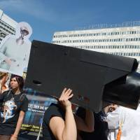 Photo - In this picture taken Sept. 7, 2013, a  woman  protests   with a selfmade surveillance camera on her head during the demonstration 'in Berlin, Germany. German news weekly Der Spiegel reports Sunday Sept. 8, 2013  that the U.S. National Security Agency can access users' data on all major smartphones.  The magazine cites internal documents from the NSA and its British counterpart GCHQ in which the agencies describe setting up dedicated teams to crack protective measures on iPhones, BlackBerry and Android devices.  This data includes contacts, call lists, SMS traffic, notes and location data.  (AP Photo/dpa,Rainer Jensen)