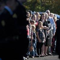 Photo - Family and friends of Spc. Sarina N. Butcher, 19, of Checotah, Okla., watch as National Guard Honor Guard members prepare to carry her casket out of the Brazzell/Cornish Funeral Home during a Friday, Nov. 11, 2011,  service in Prescott, Ark. Butcher is both the youngest  and first female Oklahoma National Guard member to die in combat in Iraq and Afghanistan during wartime. She died from wounds caused by an improvised explosive device on Nov. 1 while serving in Afghanistan.(AP Photo/ The Texarkana Gazette, Adam Sacasa)