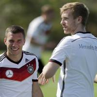 Photo - Germany's national soccer players Lukas Podolski, left, and Per Mertesacker warm up during a training session in Santo Andre near Porto Seguro, Brazil, Wednesday, June 11, 2014. Germany will play in group G of the 2014 soccer World Cup. (AP Photo/Matthias Schrader)