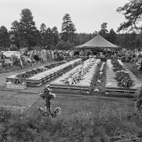 Photo - FILE - In this July 9, 1956 file photo, nearly four hundred relatives and friends of the 70 people who died in the crash of a TWA Super-Constellation over the Grand Canyon June 30, 1956 attend a mass funeral service in Flagstaff, Ariz. Sixty-seven caskets, three of the identified dead having been returned at relatives request to their homes, will be lowered into a common grave. On Tuesday, July 8, 2014, the Grand Canyon National Park will mark the designation of the crash site as a National Historic Landmark in a ceremony overlooking the gorge where the wreckage was scattered over 1.5 square miles. (AP Photo/David F. Smith, File)