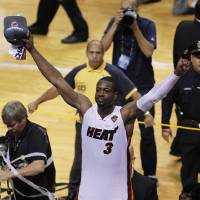 Photo -   The Miami Heat's Dwyane Wade (3) raises his arms in victory after Game 5 of the NBA finals basketball series against the Oklahoma City Thunder, Thursday, June 21, 2012, in Miami. The Heat won 121-106 to become the 2012 NBA Champions. (AP Photo/Wilfredo Lee)