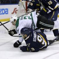 Photo - Dallas Stars' Antoine Roussel falls over St. Louis Blues' Jaden Schwartz while chasing the puck during the first period of an NHL hockey game Saturday, March 29, 2014, in St. Louis. (AP Photo/Jeff Roberson)