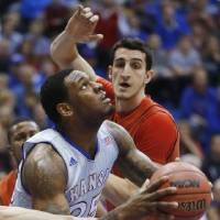 Photo - Kansas forward Tarik Black (25) is fouled while covered by Texas Tech forward Dejan Kravic, back, during the first half of an NCAA college basketball game in Lawrence, Kan., Wednesday, March 5, 2014. (AP Photo/Orlin Wagner)