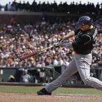 Photo - Colorado Rockies' Justin Morneau hits a two-run double off of San Francisco Giants pitcher Javier Lopez during the eighth inning of a baseball game in San Francisco, Sunday, June 15, 2014. (AP Photo/Jeff Chiu)