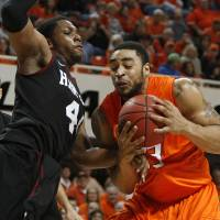Photo - Oklahoma State's Marshall Moses (33) tries to get past Harvard's Keith Wright (44) during a first round NIT game on Tuesday. Photo by Bryan Terry, The Oklahoman