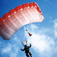 Photo - This undated photo provided by the Missoula Smokejumper Base in Missoula, Mont., shows a smokejumper descending through the air. Throughout the summer, public tours are offered daily at Missoula's  Aerial Fire Depot and Smokejumper Center, giving a look at the preparation and skill required of the smokejumpers who are trained to parachute in to attack fires in remote, rugged places. (AP Photo/Missoula Smokejumper Base)
