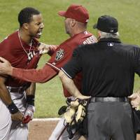 Photo -   Arizona Diamondbacks' Chris Young, left, is restrained by manager Kirk Gibson as he argues with home plate umpire Larry Vanover, right, after being ejected for arguing a called third strike for the last out in the of the top of the seventh inning of the baseball game against the Pittsburgh Pirates on Wednesday, Aug. 8, 2012, in Pittsburgh. The Pirates won 7-6. (AP Photo/Keith Srakocic)