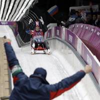 Photo - Erin Hamlin of the United States greets her coach after finishing her final run to win the bronze medalduring the women's singles luge competition at the 2014 Winter Olympics, Tuesday, Feb. 11, 2014, in Krasnaya Polyana, Russia. (AP Photo/David J. Phillip )